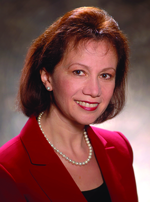 Headshot of Bella Goren, a 1983 graduate of the Chemical Engineering Department at UT Austin, wearing a red suit, black top and pearl necklace sitting in front of a gray background.