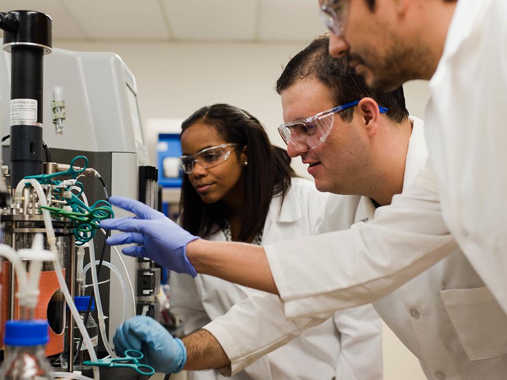 three people in lab coats looking at beaker