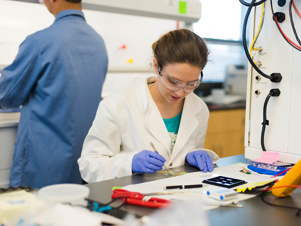 woman sitting in lab with small devices at desk