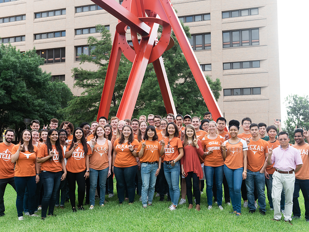 group of students in orange shirts in front of clock knot scultpure